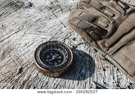 An Old Compass And Military Gloves On The Stump Of A Cut Tree.