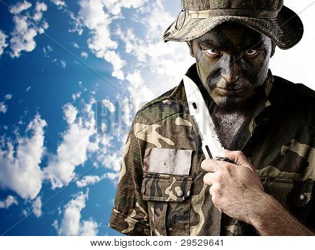 portrait of a young soldier painted with jungle camouflage threatning to suicide against a cloudy sky background