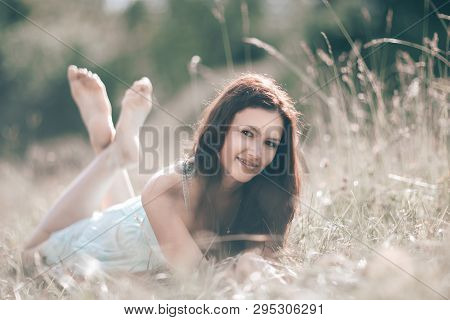 brooding young woman lying on grass on summer day. poster