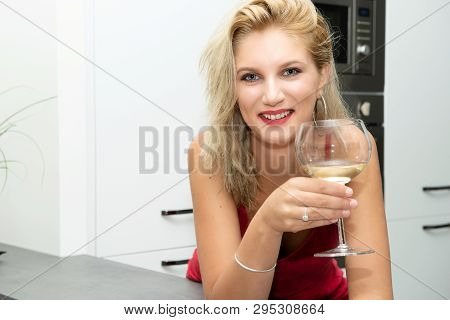 A Beautiful Young Blonde Woman With Red Dress Drinking White Wine