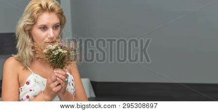 A Portrait Of Beautiful Young Blonde Woman With Bouquet Of Flowers