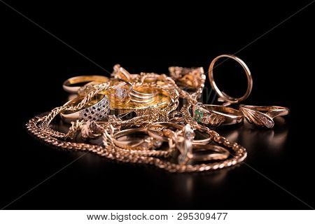 Gold Jewelry Closeup. Gold Jewelry Lie In A Heap On A Black Background.