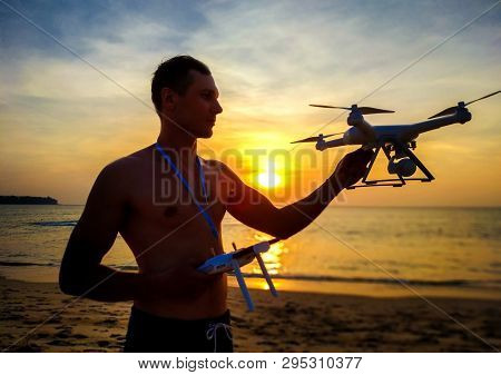 Drone Flying At Sunset Over The Sea. Man Landing The Drone Frome The Air. Sunset Photo Frome The Air