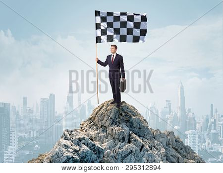 Successful businessman on the top of a city holding goal flag
