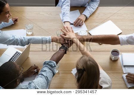 Team People Stacking Hands Together Over Table Engaged In Teambuilding