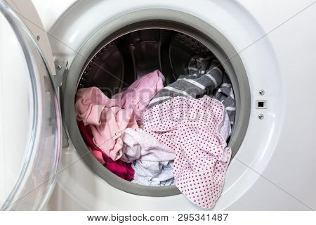 Opened Round Washing Machine Door With Rotating Garments Inside. Focus In The Center Of Dirty Laundr