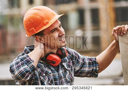 Be Careful. Construction Worker In Protective Helmet Feeling Neck Pain While Working At Construction