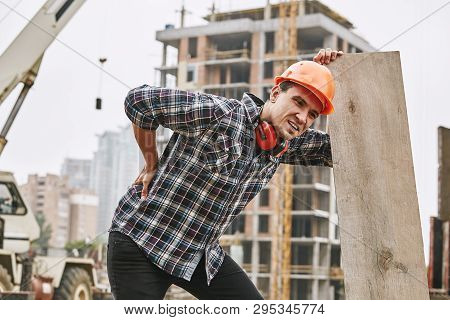 Hard Work. Construction Worker In Protective Helmet Feeling Back Pain While Working At Construction