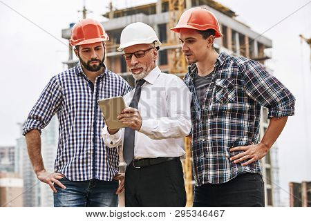 Using Modern Technologies. Senior Engineer Is Looking At Project Plan On Digital Tablet With Two You