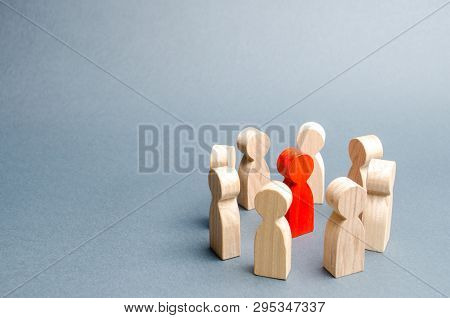 A Circle Of People Surrounds A Red Person. Communication. Business Team, Teamwork, Team Spirit. Wood