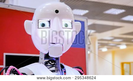 White Cute Humanoid Robot Moving Head And Hands At Technology Exhibition. Future, Emotion, Ai And Ro