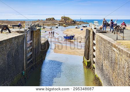 6 July 2018: Bude, Cornwall, Uk - The Canal And Lock Gates Standing Open To The Sea, As People Relax