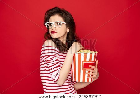 Scowling Brunette Lady Grasping Box With Pop Corn