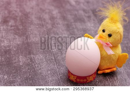 White Chicken Egg Is Located Next To Funny Yellow Fluffy Toy Chicken On Grey Background. The Concept
