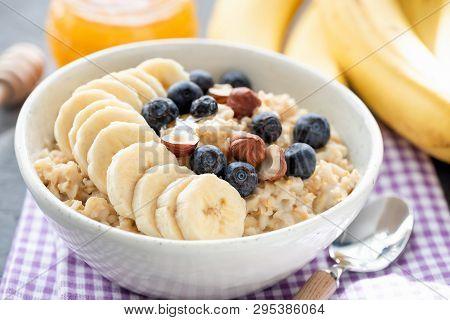 Tasty Oatmeal Porridge Bowl With Banana, Blueberry, Hazelnuts And Honey. Vegan Breakfast Food For He