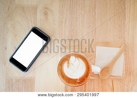 Top View Of Hot Coffee And Mobile Phone On Wood Table