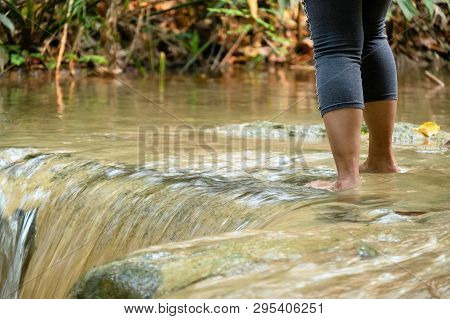 Woman Stand Relaxing In The Cold And Fresh Waterfall In The Forrest.