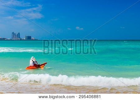 Lifeguard On Duty Seen From Behind In Orange Boat And Paddle In Hand Going Into Sea.