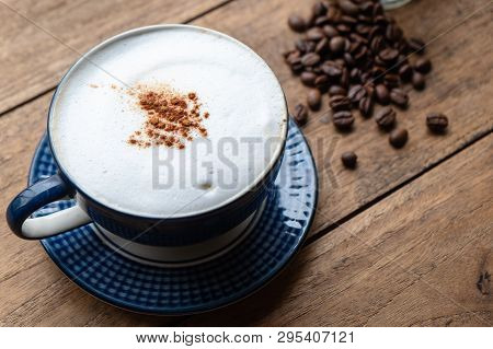 Capucino Coffee With Coffee Beans On The Old Wood Table.