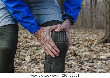 A Man In Training Clothes Got A Knee Injury While Jogging In Outdoor Workout. Concept Of Sports Inju