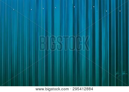 The Fence Is Made Of Metal Profile With Screws. Iron Fence. New Metal Fence. Texture Or Background.