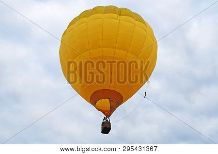 A Yellow Balloon Flies In The Blue Sky With White Clouds On A Summer Day