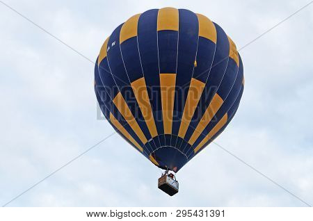Balloons Of Blue And Yellow Color Rises Into The Sky Over A Green Meadow On A Summer Day