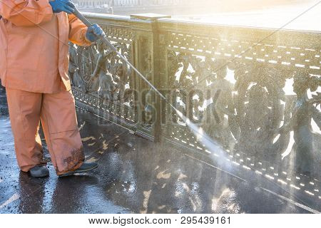 Worker Cleaning Driveway With Gasoline High Pressure Washer Splashing The Dirt, Railings, Bumpers Br