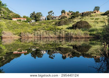 Canyon homes and rock formations reflecting in spring fed mountain pond at Santa Susana Pass State Historic Park near Los Angeles and Simi Valley in Southern California.