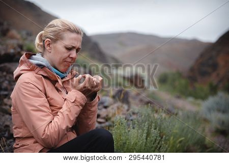A Blonde Girl In A Beige Windbreaker Sits On The Rocks Among The Red Mountains. Looks At Its Manicur