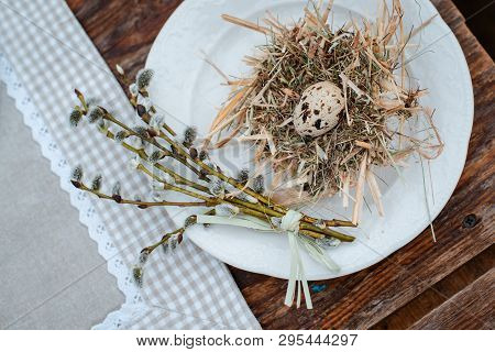 Decorative Nest Of Straw On A Plate With Easter Quail Egg On A Served Festive Table In The Garden Ou