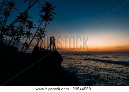 Silhouette Of Loving Couple On Sea. Man And Woman At Sunset. Honeymoon On The Islands. Man And Woman