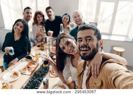 Sharing Happy Moments. Self Portrait Of Young People In Casual Wear Smiling While Having A Dinner Pa