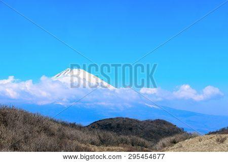 Beautiful sacred Mount Fuji (Fujiyama) in clouds on blue sky background, Japan