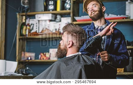 Hipster bearded client getting hairstyle. Barber on cheerful face with hairdryer styling hair of client. Barber with hairdryer works on hairstyle for bearded man, salon background. Styling concept poster