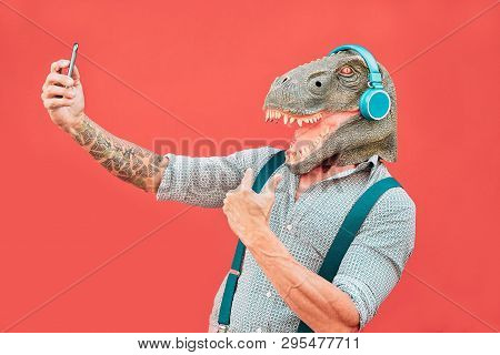 Crazy Senior Man Wearing T-rex Mask And Taking Selfie With Mobile Smartphone - Hipster Older Male Ha