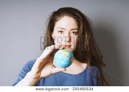 Young Woman Holding World Globe In Her Hand - Travel Or Environmental Protection Or Girl Power Conce