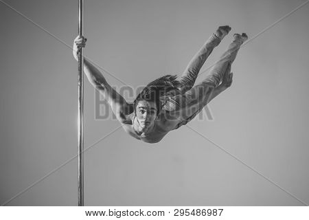Guy Makes Figure On Pole, Fly In Air. Work Out Concept. Man With Long Hair And Nude Torso Wears Deni