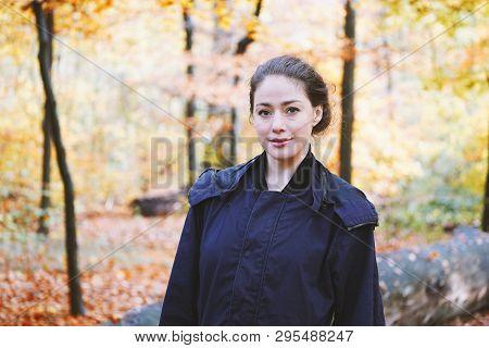 Young Woman Enjoying Nature Walk Through Forest In Autumn Season
