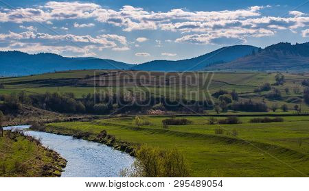 Olt River In Transylvania, Romania, Blue Mountains At Early Spring, Landscape Image.