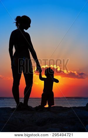 Happy Family Black Silhouette On Sunset Sky Background. Young Mother, Baby Son Have Fun Together, Wa