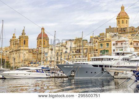 Birgu, Malta - March 09, 2018: Vittoriosa Yacht Marina With Luxury Yachts, Sailboats And Birgu Archi