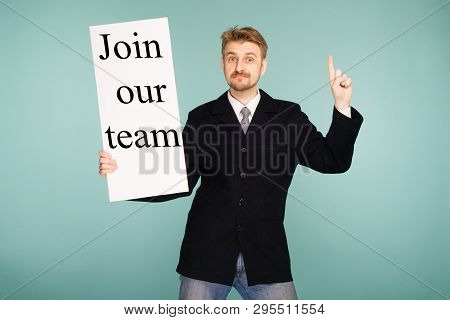 Happy Smiling Young Business Man Showing Signboard With Sign Join Our Team, On Blue Background