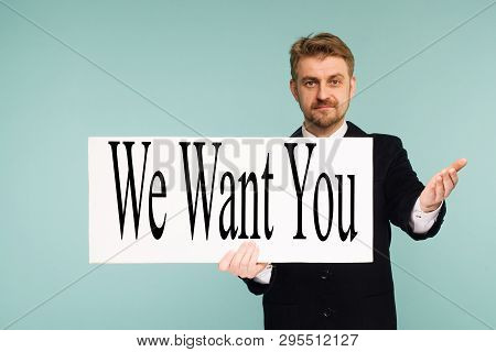 Happy Smiling Young Business Man Showing Signboard With Sign We Want You, On Blue Background