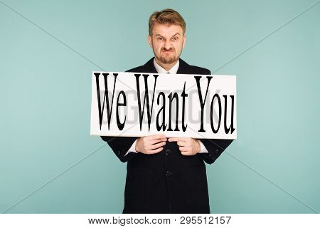 Angry Beard Young Business Man Showing Signboard With Sign We Want You, On Blue Background