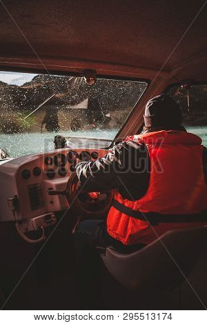 Boat Captain In Life Jacket Steering A Boat During A Rainstorm.