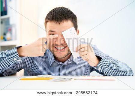 Photo of happy man with lottery ticket sitting at table.