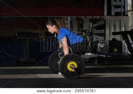Young fit woman doing deadlift workout with heavy barbell in dark gym