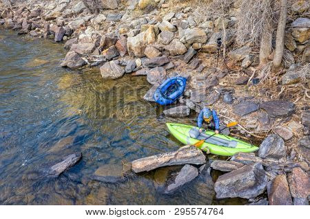 aerial view of inflatable whitewater kayak, packraft, camera on tripod and a paddler on a rocky shore of the Poudre River in Colorado