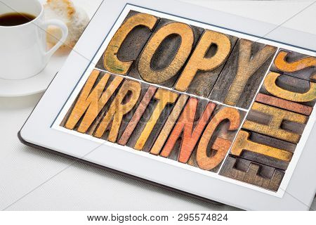 copywriting ethics -  word abstract in vintage letterpress wood type on a digital tablet with a cup of coffee